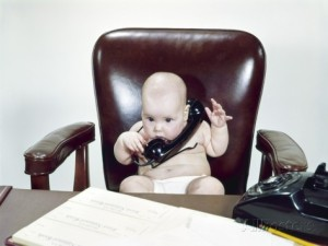 h-armstrong-roberts-1960s-chubby-baby-sitting-in-leather-office-chair-behind-desk-holding-talking-on-telephone